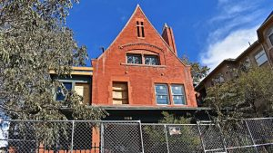 photo shows the peabody-whitehead mansion, surrounded by a wire fence and with its top two windows boarded up.