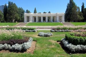 Photo shows the pavilion at Cheesman Park and Denver Botanic Gardens. It has rows of large while marble columns. Small shrubs and plants are in the foreground.
