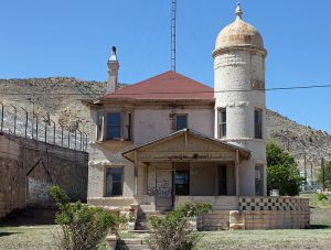Photo shows the Deputy Warden's house built by prison labor. It has a cream stucco exterior and a red roof. A large tower is on the right of the home, and a wrap around porch surrounds the house.