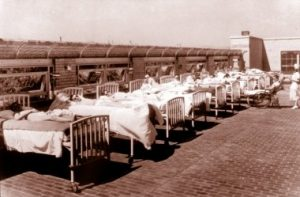 Photo shows a line of hospital beds set up outside on the roof of the hospital. There are children lying in the beds with a nurse checking them down the line.