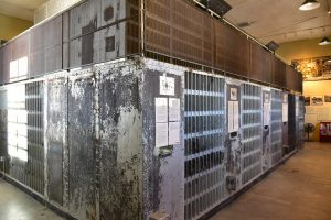 Photo shows one of the cellblocks in the jail, with the paint peeling off at one side and metal bars across the front.