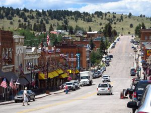 Photo shows modern day Cripple Creek, with a bustling main street lined with cars and people walking.
