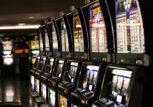 Photo shows a line of colorful slot machines similar to the ones that the spirit of Maggie uses.