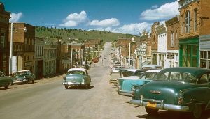 Photo shows the streets of Cripple Creek as they looked in 1957. Classic cars of all shapes and models are seen on the side of the street. Brick buildings line the street.