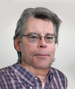Photo shows author Steven King in a plaid shirt, with a plain white background. He is smiling.