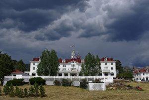 One side of the Stanley Hotel, with a red roof and stark white painted sides. A stormy sky hovers above.